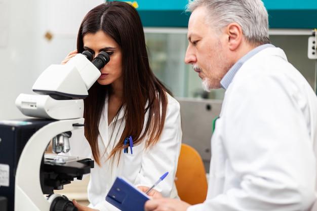 Пара ученых, исследующих в лаборатории