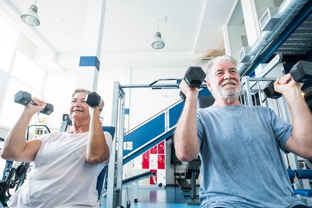 Пара пожилых людей и пенсионер в тренажерном зале вместе делают упражнения - мужчина и женщина держат гантели, чтобы быть здоровым и фитнес-образ жизни и концепция - два зрелых человека