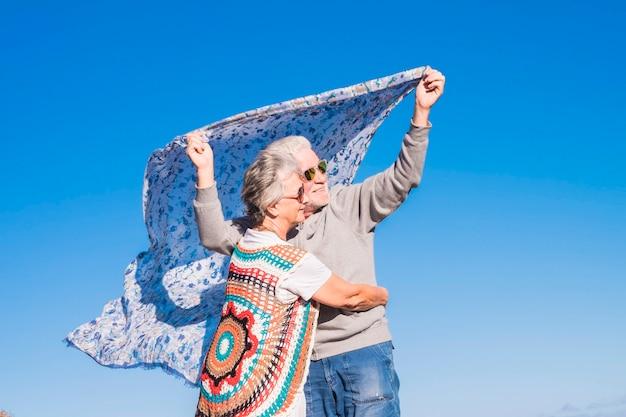 テネリフェ島の岩の多いビーチで、白人のヒッピースタイルと人生のカップルが休んでいます。海の近くの完全な自由の概念のための色と代替のライフスタイル。生きるための代替のカラフルな服f