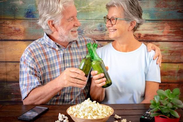 맥주와 팝콘 재미 수석 커플. 앉아서 나무 테이블에 웃 고. 손에 맥주 병에 집중