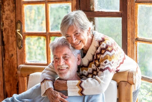 高齢の成熟した人々のカップルは、抱き合ったり愛したりして一緒に家で時間を楽しんでいます。恋に老人と老婆の肖像画。永遠の命と幸せな高齢者の概念