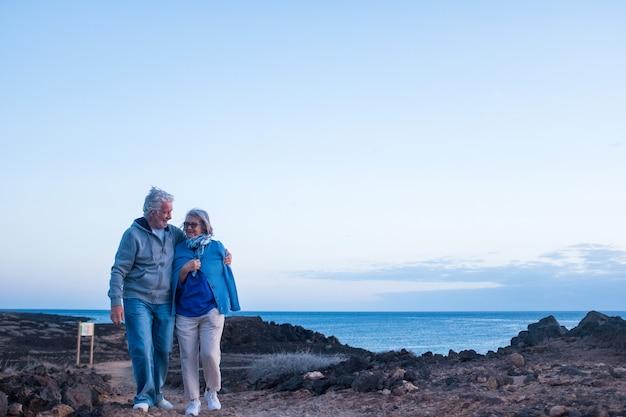 夕方の背景に海または海と岩のビーチで隔離された一緒に歩くシニアのカップル-愛と愛情の概念とライフスタイル-成熟した男性と女性の散歩