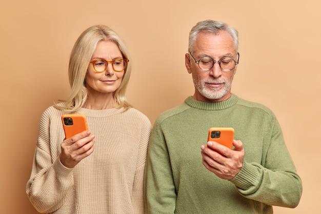 수석 여자와 남자의 커플은 디스플레이에 초점을 맞춘 현대 스마트 폰을 사용하여 뉴스 온라인 착용 캐주얼 점퍼를 갈색 스튜디오 벽 위에 절연