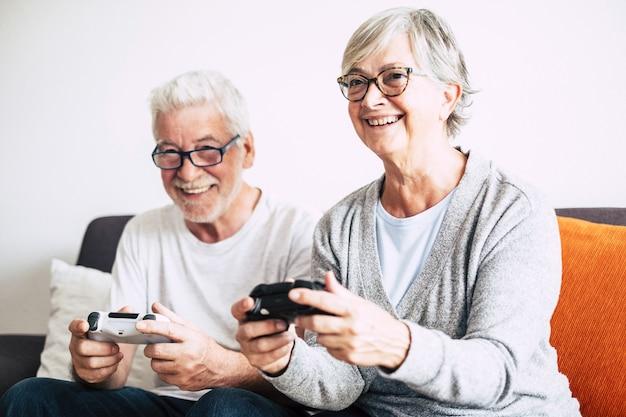 Пара пожилых людей и пожилых людей смотрят телевизор и используют контроллеры, играя в видеоигры дома вместе на диване - изолированный образ жизни в помещении