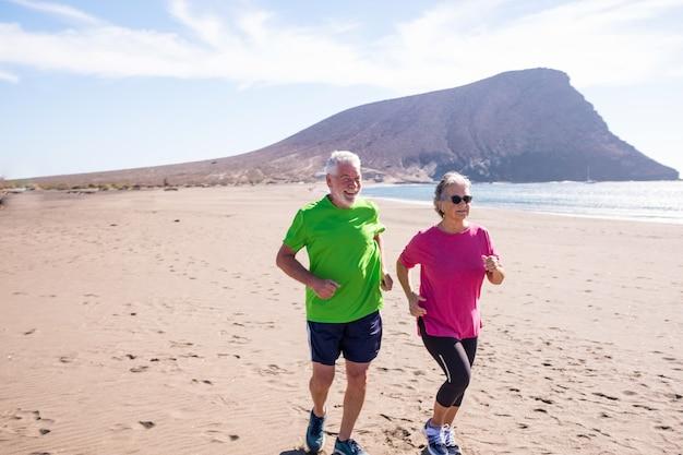 노년층과 성숙한 사람들이 해변에서 모래사장에서 함께 뛰고 조깅하는 것 - 건강하고 건강한 생활 방식과 개념 - 활동적인 연금 수급자들이 즐기고 운동을 하고 있습니다.