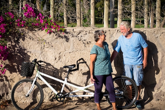 乗る準備ができている美しくて面白い白いタンデムで公園で立ち止まった先輩と成熟した人々のカップル-乗車後少し休憩