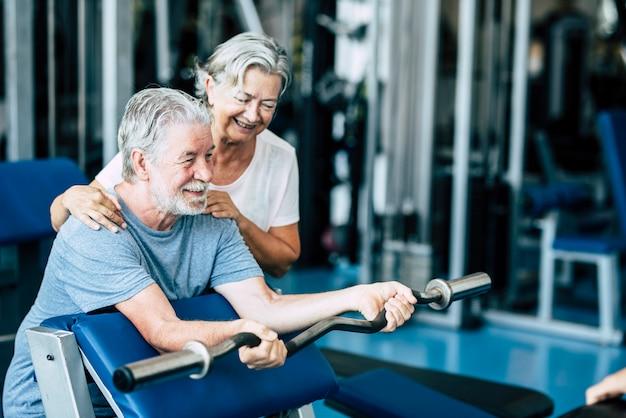 Пара пожилых людей и зрелых людей вместе тренируются в тренажерном зале, чтобы тренировать свое тело - женщина помогает взрослому мужчине делать упражнения