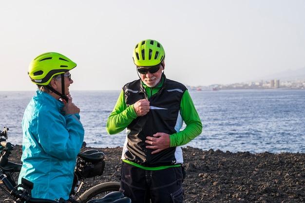 바다와 해변을 배경으로 산에서 자전거를 탈 준비를 하는 노인과 연금 수령자 두 명 - 운동을 할 준비가 된 두 명의 성숙한 사람