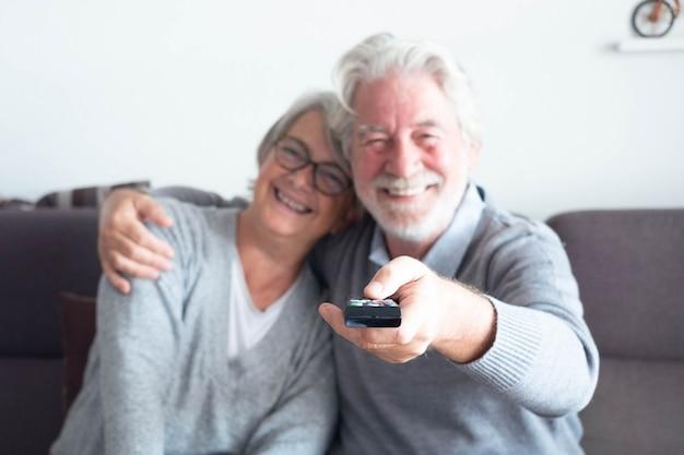 Пара пожилых людей и пенсионеров вместе дома смотрят телевизор и смотрят какую-то реальность или программу - счастливые два человека на диване - зрелый мужчина держит пульт