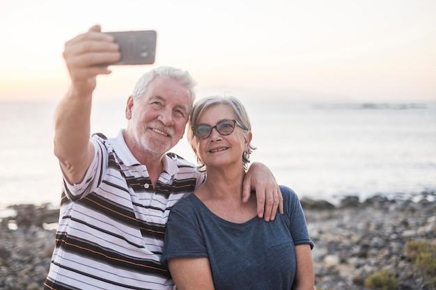 Пара пожилых людей на пляже, делающие фото вместе - женщина в очках и пенсионер - селфи на пляже - развлекайтесь и наслаждайтесь - кавказская 602