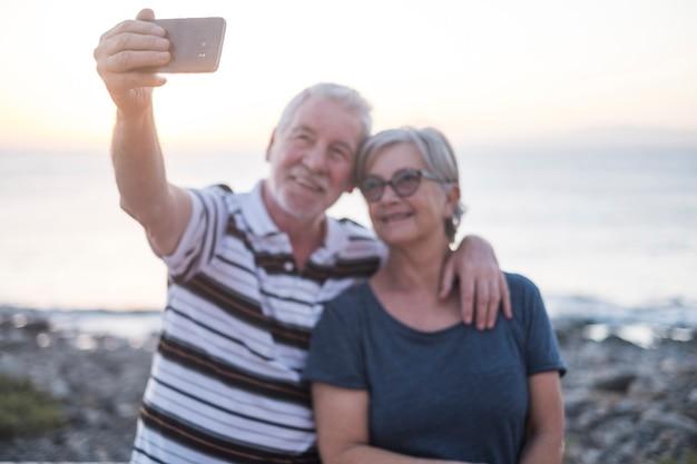 一緒に写真を撮るビーチの先輩のカップル-眼鏡をかけた女性と引退した男性-ビーチでの自分撮り-楽しんで楽しんでください-白人