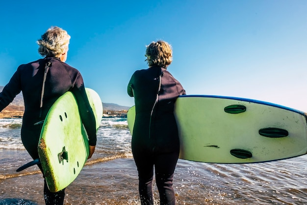 해변에서 서핑을 할 준비가 된 서핑 테이블을 들고 검은 잠수복을 입은 노인 부부 - 휴가나 자유 시간에 함께 행복한 활동을 하는 활동적인 성숙한 은퇴한 사람들