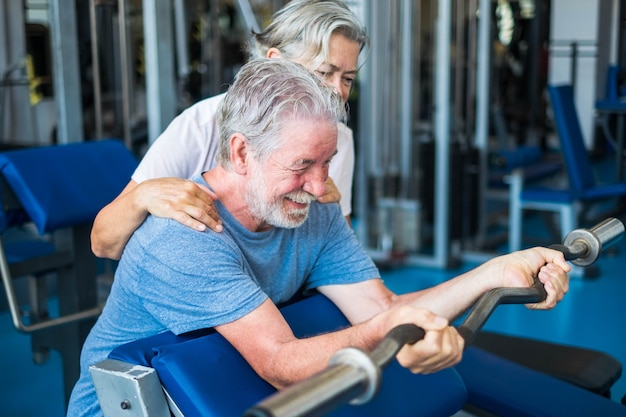 Пара пожилых людей в тренажерном зале вместе делают упражнения - зрелая женщина смотрит и помогает своему мужу удерживать штангу и поднимать тяжести