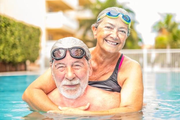 여름을 즐기고 수영장에서 함께 수영하고 웃는 노인 부부