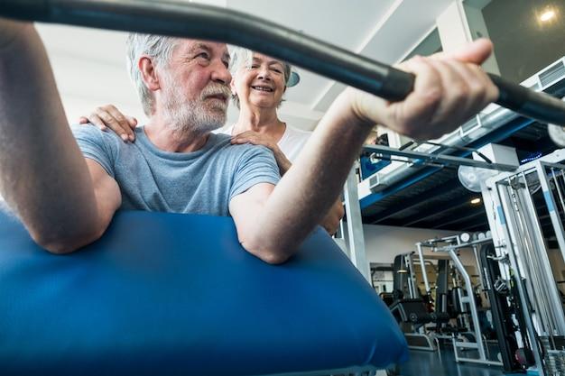 Пара пожилых людей развлекаются и вместе делают упражнения в тренажерном зале, поднимая тяжести - два счастливых пенсионера делают тренировки, чтобы быть в форме и здоровыми