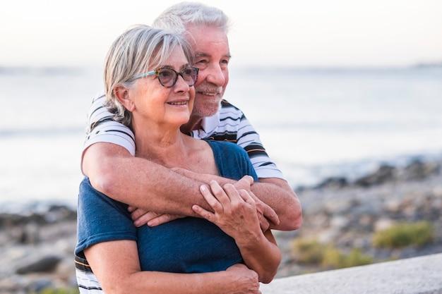 Пара пожилых людей на пляже с большой любовью - пенсионеры вместе - женщина в очках и мужчина с морским фоном