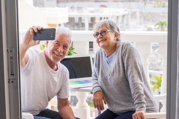 그들의 테라스에 있는 노인 부부는 노트북을 들고 함께 셀카를 찍고 앉아 - 편안한 성숙한 은퇴한 여성과 사진을 찍는 남성