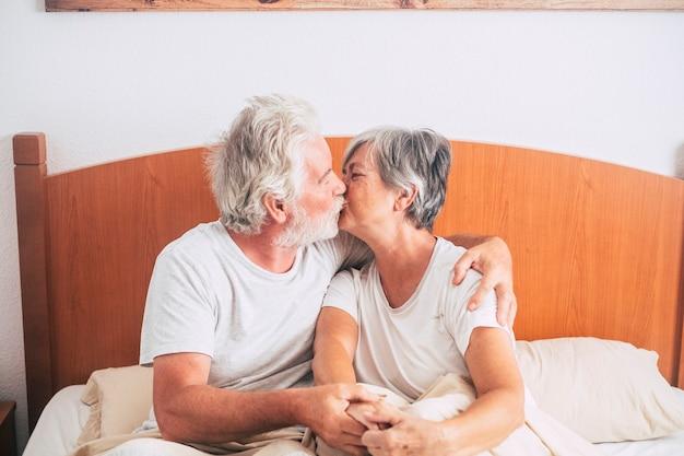 彼女が彼にキスしている間、愛と影響を持って見たり笑ったりしている先輩のカップル-起き上がる前の朝に寝室で結婚した引退した成熟した大人