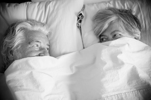 Пара пожилых людей смотрит между ними и с любовью улыбаются и аффектно улыбаются под одеялом у кровати - пожилые и пенсионеры поженились в спальне утром перед тем, как встать.