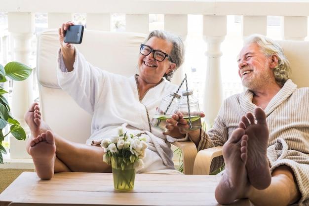 ホテルや家のリゾートスパでカクテルを飲みながら携帯電話でサルフィーを飲んでいる高齢者や成熟した人々のカップル-テーブルの上で足を見て楽しんでいます