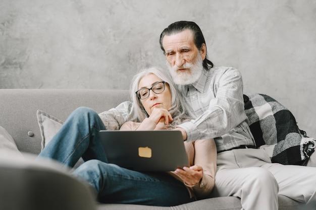 笑顔で同じラップトップを見て、ソファの封鎖と検疫のライフスタイルに抱きしめられた先輩のカップル