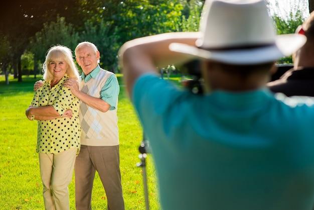 Пара пожилых людей стоя на открытом воздухе.