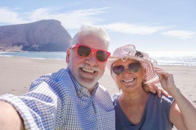 산을 배경으로 아름다운 해변에서 여행을 하고 셀카를 찍는 노인 부부 - 선글라스를 끼고 카메라를 바라보며 웃고 즐기는 - 휴가 생활 방식
