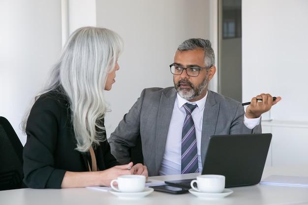 ノートパソコン、ドキュメント、コーヒーを片手にテーブルに座って話している真面目な同僚のカップル。ミディアムショット。チームワークとコミュニケーションの概念