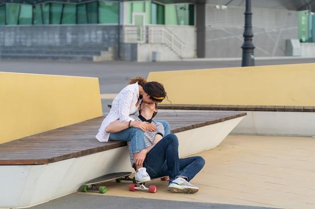 키스하는 스케이터 커플은 도시 공간 청소년 로맨스와 사랑에서 야외에서 함께 롱보드에 앉아 있다