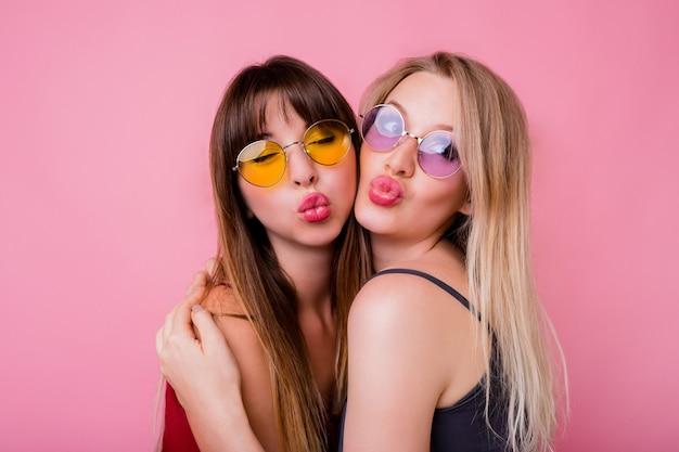 키스를 보내고 분홍색 벽에 포즈 웃는 여자의 커플