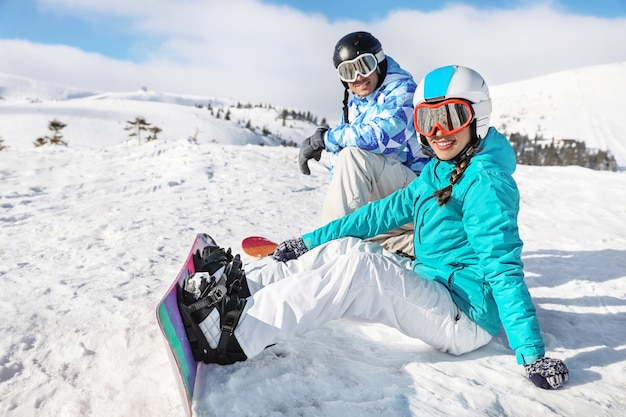 Пара сноубордистов на лыжной трассе на заснеженном курорте. зимние каникулы