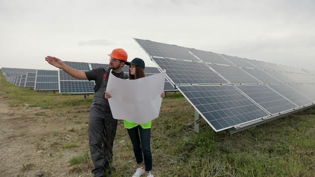 맑은 전력 에너지 생산을 위한 투자 보고서를 제어하고 학습하는 데 협력하는 두 명의 전문가. 녹색 에너지의 개념입니다. 녹색 에너지 개념입니다. 태양광 패널 분야.