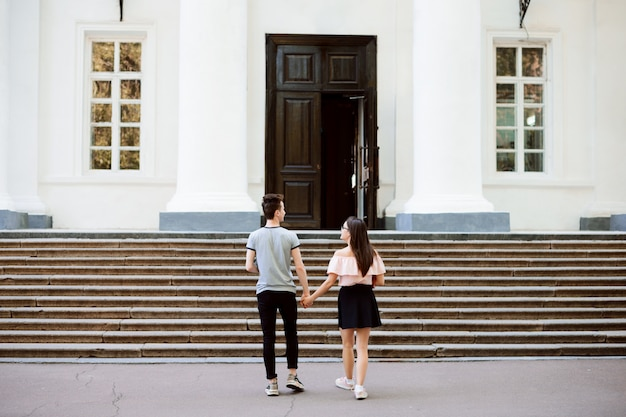 Пара влюбленных студентов уверенно идет в обычный университет, держа друг друга за руку, готовясь к новому дню обучения