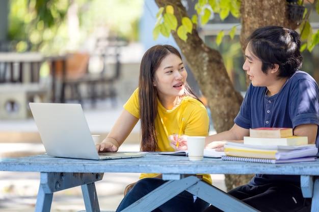 Пара студентов сидят и используют ноутбук в университете на открытом воздухе, проводят онлайн-исследования Premium Фотографии