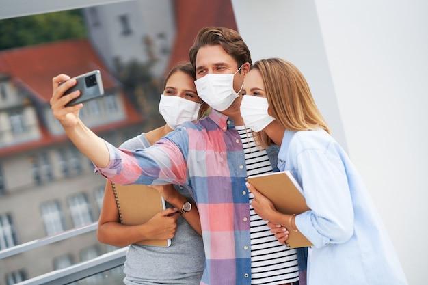 キャンパスで自分撮りをしながらマスクを着用している学生のカップル