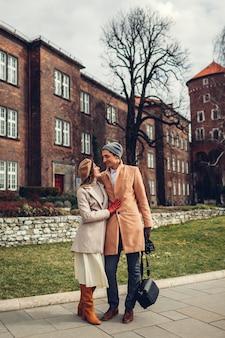 ポーランド、クラクフのヴァヴェル城の建築を楽しんでハグを歩くスタイリッシュな観光客のカップル。