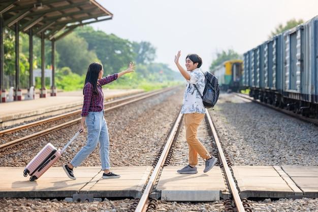 バックパックを持って屋外の地下鉄駅で電車に乗るスタイリッシュな観光客のカップル、タイの鉄道駅のビンテージスタイルのコンセプトを旅行するアジアのカップル