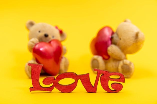 テディベアのおもちゃのカップルと木製の文字、赤いハートからの愛という言葉。バレンタインデーのコンセプト。はがきテンプレート。