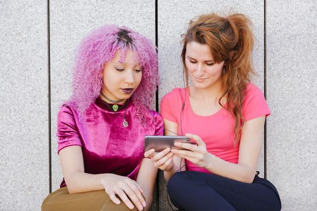 Пары подростка деля наушники и слушая музыку на их телефоне