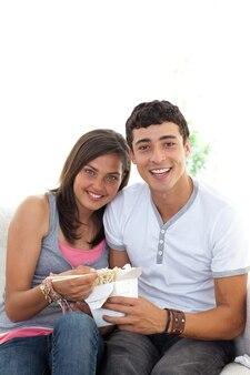 Пара подростков едят макароны с копией пространства