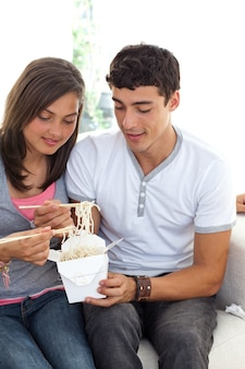 Пара подростков едят макароны
