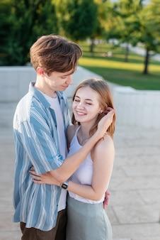 手をつないで公園で抱き締めるティーンエイジャーのカップル初恋