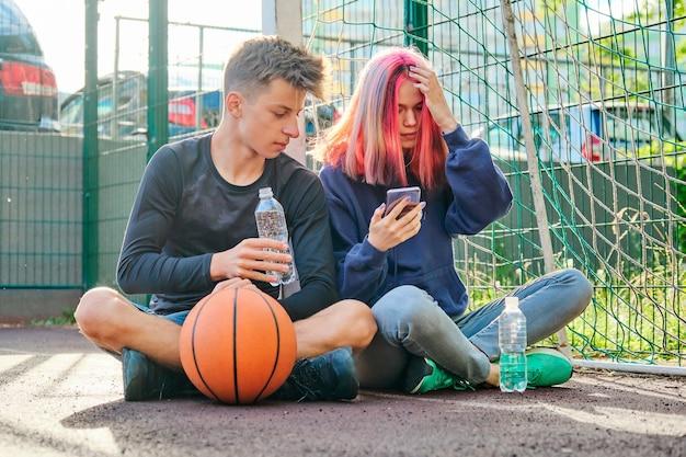 Пара подростков на спортивной уличной площадке с мячом, образ жизни, мальчик и девочка 16 лет разговаривают, пьют воду из бутылки, глядя на экран смартфона