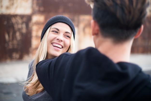 Пара подростков веселится и смеется вместе в городской зоне на улице - женщина в шляпе улыбается, глядя на мальчика рядом с ней