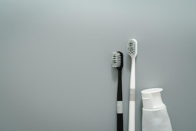 Пары зубной щетки с зубной пастой на серой предпосылке, концепции здравоохранения