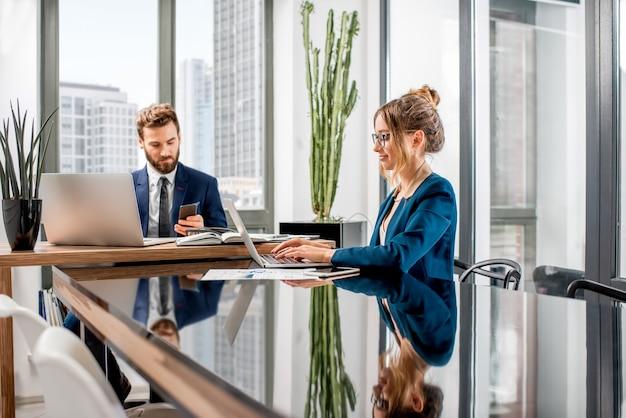 고층 빌딩의 아름다운 전망을 감상할 수 있는 고급 사무실 내부에 앉아 노트북과 문서 작업을 하는 최고 관리자 몇 명