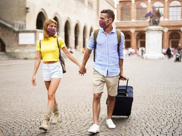 Covid19から保護するためにフェイスマスクを着用している観光客のカップルが週末の休日に街を歩いています。