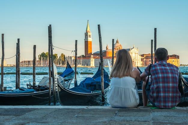 Пара туристов сидят у канала с гондолами в венеции, италия.