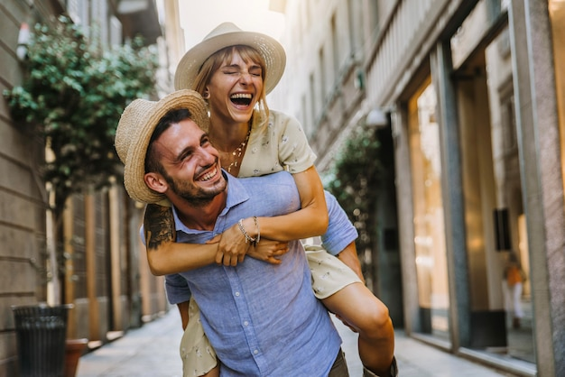 休日に街の通りを歩いて楽しんでいる観光客のカップル