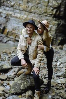 Пара туристов во время поездки останавливается и любуется красивыми горными пейзажами. девушка обнимает парня. понятие любви, нежности и отдыха